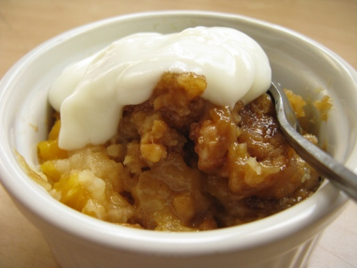 Peach dump cake topped with yogurt